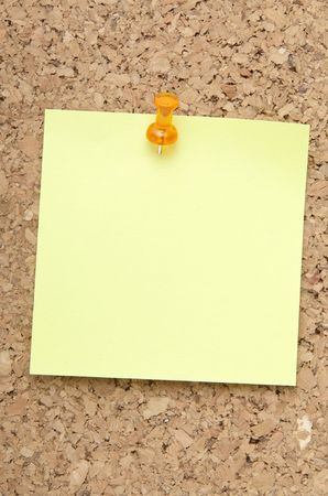 inclined: green reminder note with orange pin on corkboard