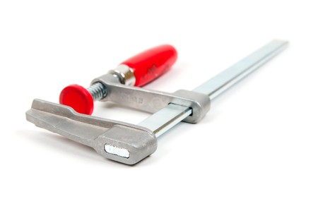 Metal vice with red handle on white background photo