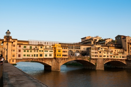 sightseeng: FLORENCE, ITALY - JUNE 2010. Crowds of tourists visit the Ponte Vecchio (Old Bridge) which is a Medieval bridge over the Arno River at evening.  Florence, Tuscany, Italy.