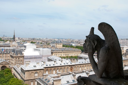 Famous Chimera (Stryge) overlooking the Paris from Notre Dame of Paris photo