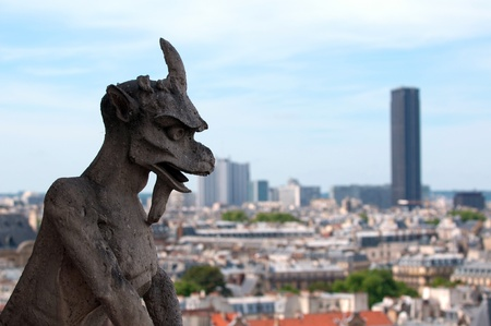 Famous Chimera (demon) overlooking the Montparnasse Tower from Notre Dame of Paris photo
