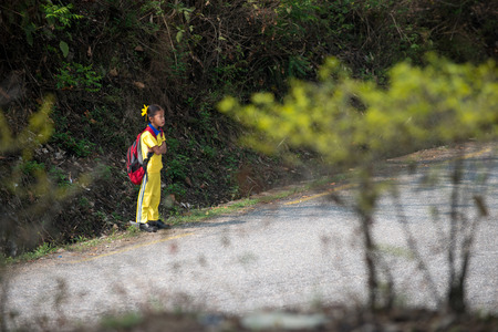 indigence: POKHARA, NEPAL - MAY 08, 2014; Unidentified small girl which waiting for a school bus on a road near the Pokhara on 08 May 2014 Editorial