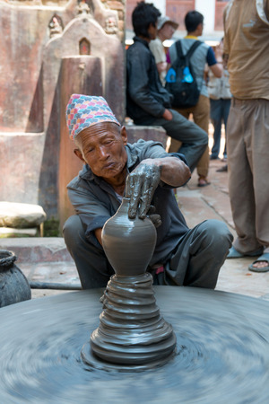 indigence: BHAKTAPUR, NEPAL - MAY 09, 2014; Unidentified pottery man on a small street near Bhaktapur durbar square on 09 May 2014