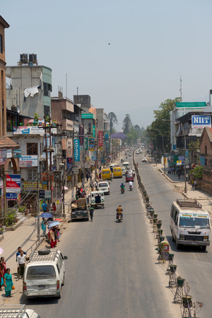 KATHMANDU, NEPAL - MAY 10, 2014: The typical street in a center of Kathmandu. Many peoples, cars and and bikes moving through the streets