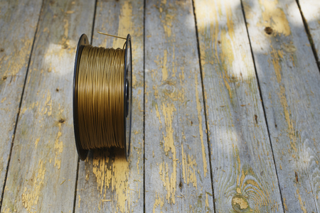 filament: Gold filament for 3D Printer on old wooden table, selective focus