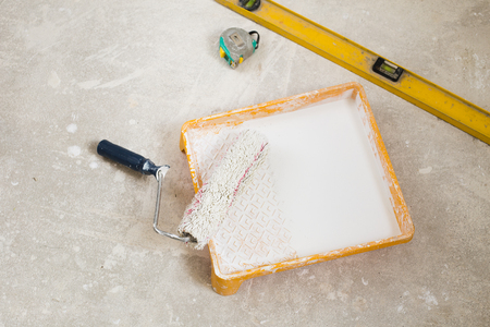 paintroller: Yellow plastic paint tray with painter roller brush on the floor