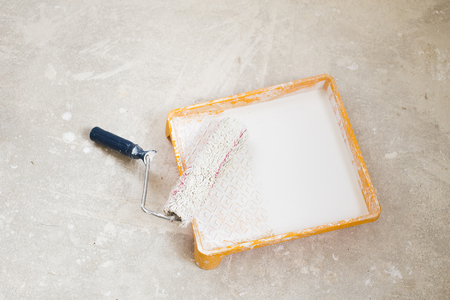 paintroller: White paint roller with tray on floor