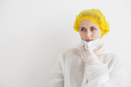 Young scientist in white protective suit holding mask with hand