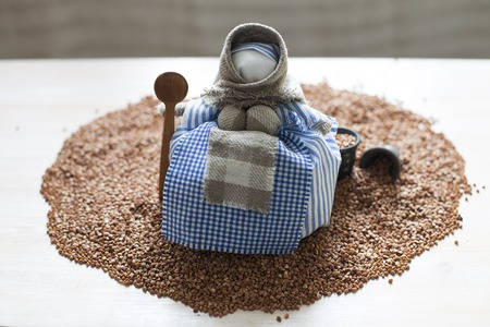 Doll with spoon on buckwheat heap