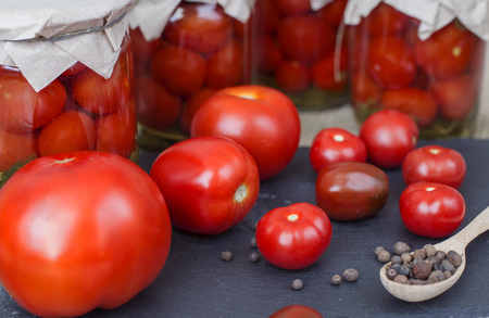 Fresh and canned tomatoes with wooden spoon Stock Photo