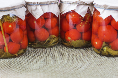 Glass jars full of canned tomatoes