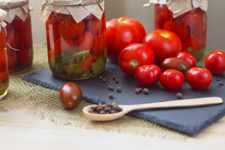 Glass jars full of tomatoes - homemade canned tomatoes and pepper peas