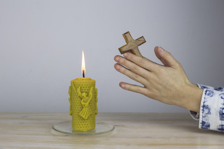 Female hands in prayer hold a wooden cross