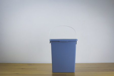 Garbage can with a gray lid stands on a white wall background