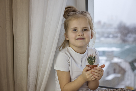 A little girl lovingly holds in her hands a cactus sitting on the windowsill