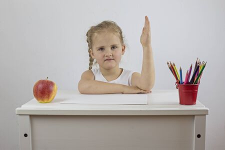 Mock up girl first day of school sitting at her desk and holding her hand up