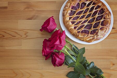 Red roses and cherry pie on a wooden table, top view and place for text