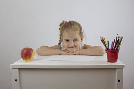 Schoolgirl at her desk with a cheerful facial expression
