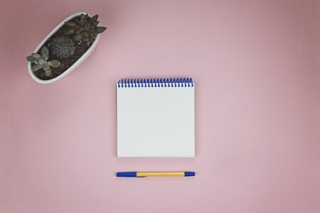Notepad with white pages and pen on a pink background