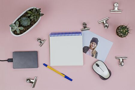 Workplace of the womens table with metal clothespins, external hard drive, succulents, mouse, telephone, open notepad and photo on a pink background