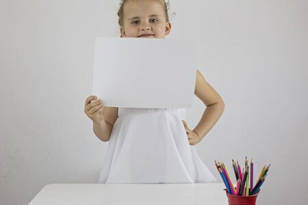 The little girl is standing at the desk and holding a white sheet of paper