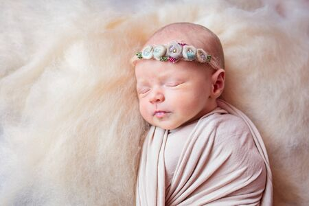 Beautiful sleeping newborn girl with a bandage of flowers on her head Stok Fotoğraf