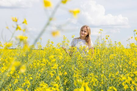 An attractive girl is standing in a rapeseed field and smiling