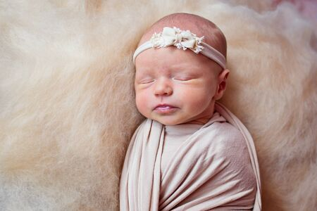 Portrait of a beautiful sleeping newborn girl with a bandage on his head