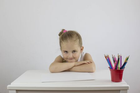 A little girl with a sly smile sits at a white desk Stok Fotoğraf