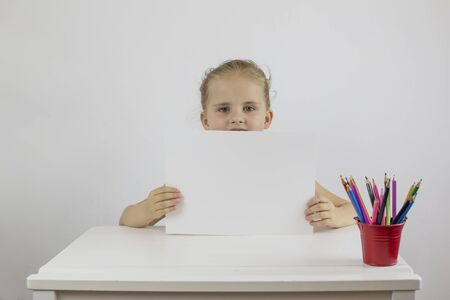 Little schoolgirl sitting at her desk t holding a white sheet of paper