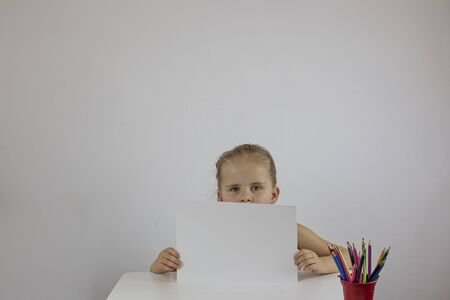 Girl holding a white sheet, sitting at a desk on a white wall Stok Fotoğraf