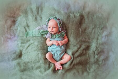 Newborn little girl in a beautiful suit on a green background Stok Fotoğraf