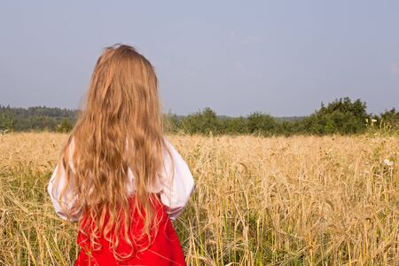 Little girl with long hair stands with her back