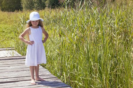 Little girl in a hat stands on a bridge surrounded by tall reeds