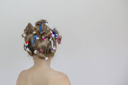 The child stands with his back, and multi-colored curlers on his hair
