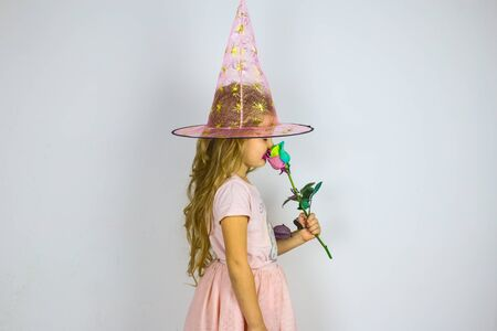 Little girl in a magic hat sniffs a rose