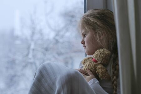 Lonely and hurt child sits and looks out the window