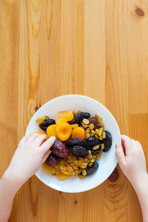Children's hands hold a plate with dried fruits. Healthy food, vitamins