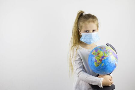 Sad child in a medical mask holds a globe