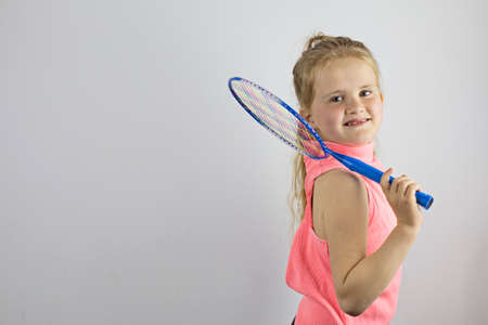 Beautiful little girl holding a tennis racket and smiling