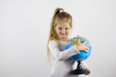 A happy child holds a globe in his hands and explores the countries he wants to go to 写真素材 - 155032857