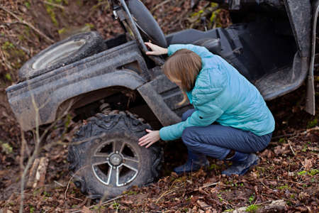A woman checks the tires of a buggy that has rolled down a mountain into a ditch