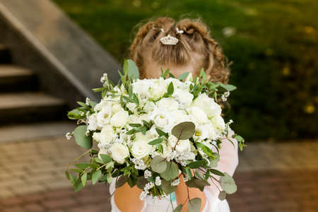 Little girl holding a bridal bouquet in her hands 写真素材 - 155712428
