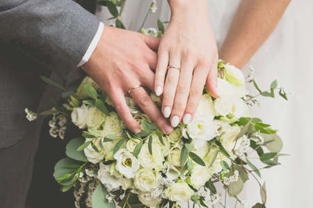 Hands of the bride and groom on a bouquet of flowers 写真素材