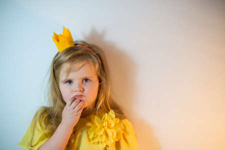 A little girl with a crown on her head and in an elegant dress looks thoughtfully into the camera