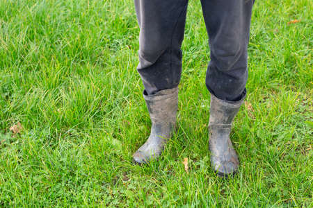 Male feet in rubber boots after work