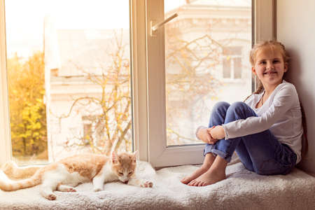 The child smiles and looks at the camera, a beautiful cat is sitting next to it.
