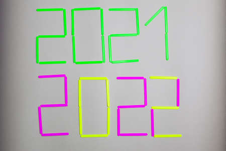 It is written 2020, 2021 with sticks of acid-green, pink, yellow colors