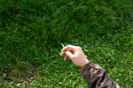 Cigarette in a mans hand on a background of summer grass. 写真素材 - 158828985