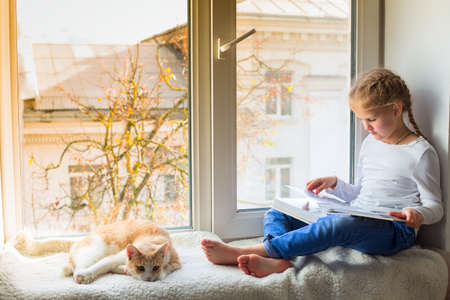 The child is looking at a book while sitting on the windowsill, and her pet is lying nearby 写真素材 - 158813828
